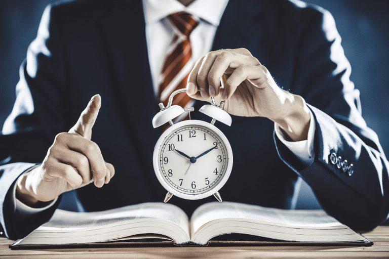 Manager mit Uhr in der Hand - Symbolisch: Minusstunden im Arbeitsrecht